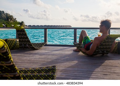 The successful man man chilling in the beach bar on Maldives