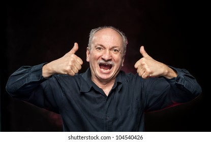 Successful man cries and shows ok sigh on dark background
