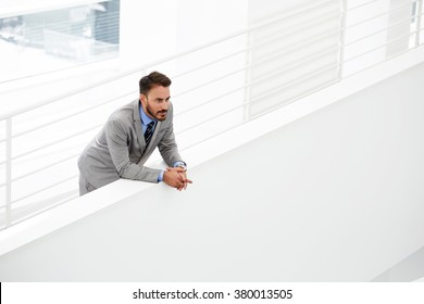 Successful man entrepreneur dressed in luxury suit looking on copy space while standing in office interior, young male manager in formal wear thinking about something serious after meeting with boss