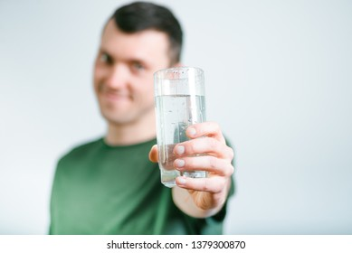 successful man gives drink a glass of water, studio photo over background