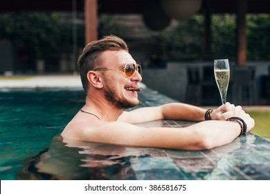 The successful man has a rest in the pool with champagne and a cigar
