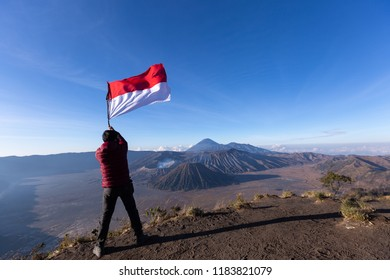 successful man hiker holding flag indonesia at cliff edge on mountain top of volcano bromo Indonesia travel at sunrise time.
