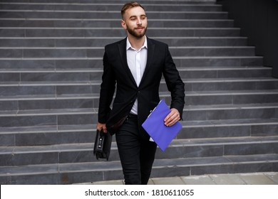 successful man hold briefcase and documents walk