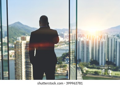Successful man lawyer talking on his cell telephone, while is standing in office interior near big window with view of business center with skyscrapers background. Copy space area for your advertising