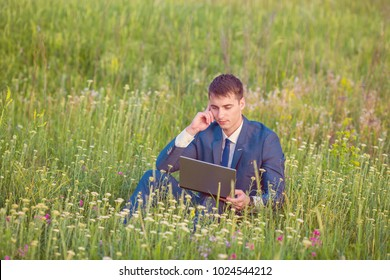 Successful man on the field with laptop