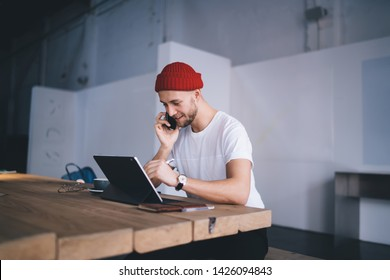 Successful man phoning to friend via application on cellphone device while drawing sketch with stylus pen on graphic tablet for painters, positive hipster guy using touch pad for remote work