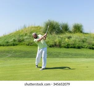 Successful man playing golf at club