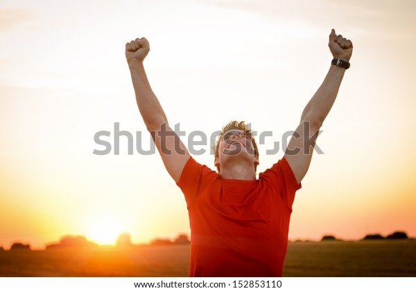 Successful man raising arms after cross track running on summer sunset. Fitness male athlete with arms up celebrating success and goals after sport exercising and working out.