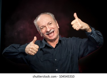 Successful man shows ok sigh on dark background