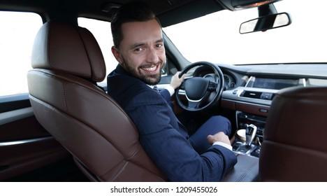 Successful man sitting behind the wheel of a prestigious car