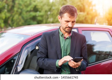 Successful man standing by the car and writing text messages on a mobile phone