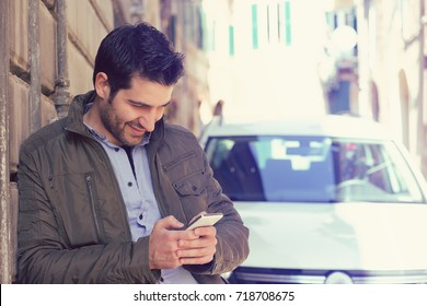 Successful man standing by his car texting on mobile phone