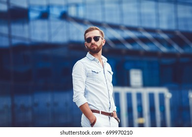 Successful man in stylish shirt posing against blue background outdoors