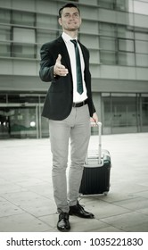 Successful man in suit with suitcase is meeting his partner in another city.