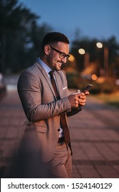 Successful man in a suit using smart phone on a street, portrait.