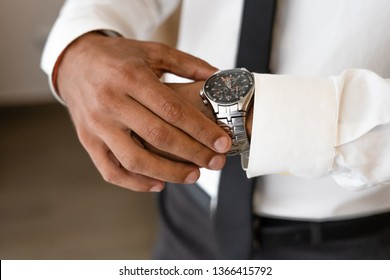 Successful man with white shirt and necktie looks on watch