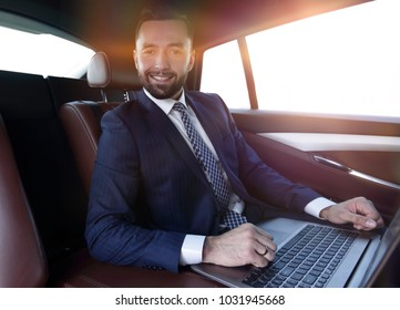 successful man working with laptop sitting in car