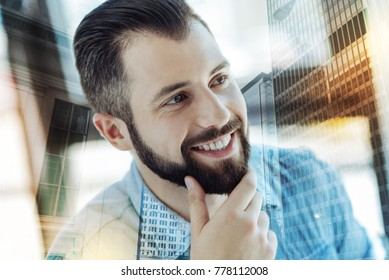 Successful man. Young busy perspective man holding hand near beard smiling and looking aside.