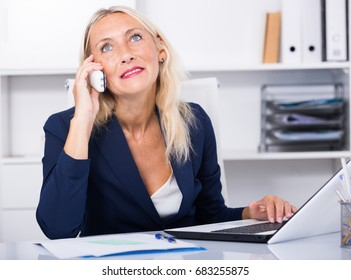 Successful mature business woman using phone and laptop at workplace