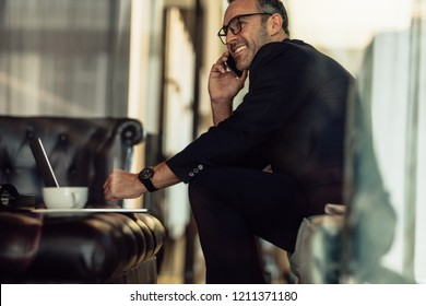 Successful mature businessman sitting in hotel lobby talking on cellphone. Happy man in business suit working from hotel lobby.