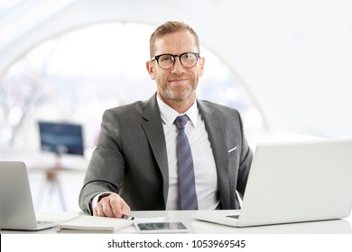 Successful mature executive financial director businessman wearing suit and looking at camera while sitting at office in front of laptop.