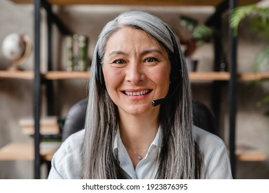 Successful mature grey-haired woman working as a it-support in call centre