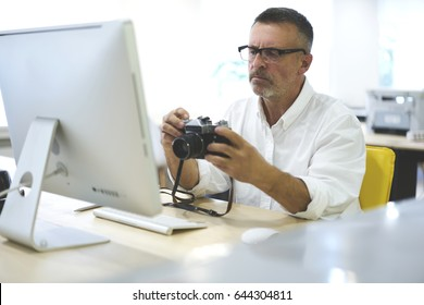 Successful mature male architector taking picture of graphic planning office building on vintage camera for future work on new project sitting in office at modern computer wit high speed internet