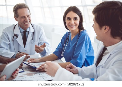 Successful medical doctors are discussing diagnosis and smiling during the conference