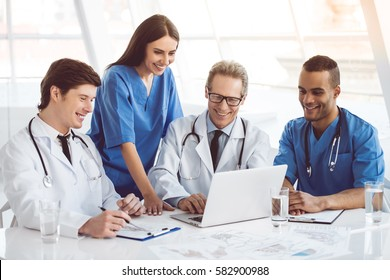 Successful medical doctors are using a laptop and smiling while having a discussion