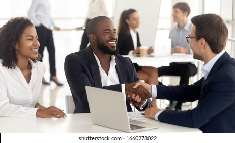 Successful meeting with happy family and realtor at office. Smiling african american man with wife shaking hands with businessman, success deal, diverse couple at negotiation with insurance employee