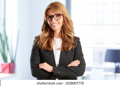 Successful middle aged financial advisor businesswoman with toothy smile looking at camera while standing at the office befor business meeting.