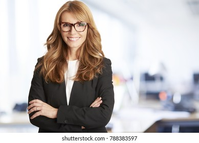 A successful middle aged financial director businesswoman standing with arms crossed at the boardroom.