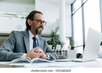 Successful middle aged male manager or ceo talks with colleagues at online conference, planning new project. Elegant businessman is using laptop, communication concept