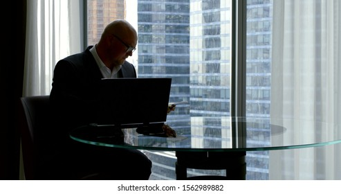 A successful middle aged man looks at documents sitting at a glass Desk and laptop in his office