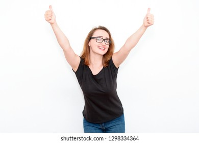 Successful modern smiling redhead woman in black glasses and casual clothes shows thumbs up on the light background. Concept of business and success.