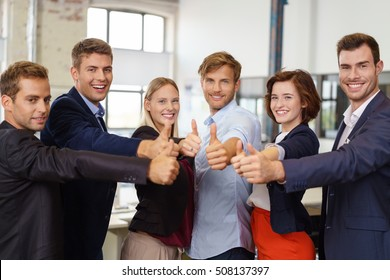 Successful motivated business team of diverse young people giving a thumbs up gesture of approval with broad smiles as they pose in the office