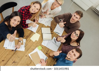 Successful motivated group of young businesspeople seated around a table looking up at the camera with happy smiles giving a thumbs up gesture