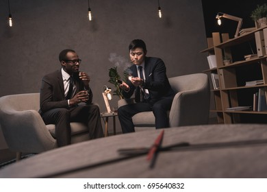 successful multiethic businessmen smoking cigars
