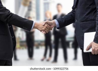Successful negotiating business concept, Businessmen shaking hands after finishing meeting or setting  goals and planning way to success in front of team work background