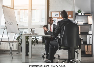 Successful negotiation. Optimistic young qualified african businessman is looking at his skilled partner with smile while sitting at table and having pleasant communication. Copy space