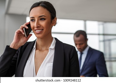 Successful negotiations. Portrait of gorgeous elegant businesswoman is standing and talking on smartphone. She is looking aside with smile while african man is standing in background