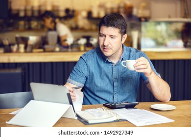 Successful new restaurant owner checking monthly reports online on tablet – middle aged man calculating bills and expenses of his small business - Startup entrepreneur stressed about financial reports