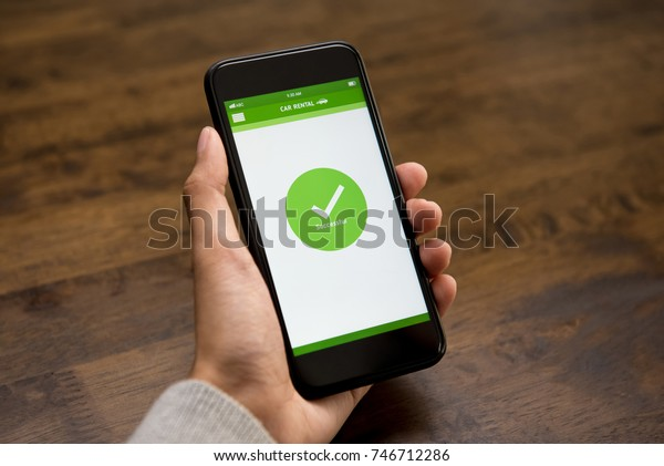 Successful online car rental confirmation sign appears on smartphone screen after booking digitally by a woman customer