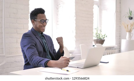 Successful Online Shopping via Credit Card on Laptop by African Man