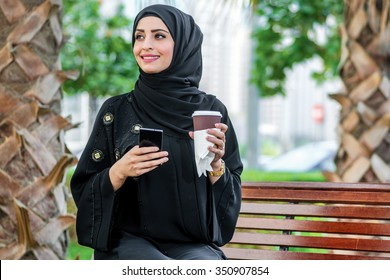 Successful operation. Arab businesswomen in hijab holding a coffee in the street and holding a cell phone against the backdrop of the skyscrapers of Dubai and is looking to the side.