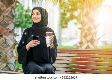 Successful operation. Arab businesswomen in hijab holding a coffee in the street and holding a cell phone around skyscrapers of Dubai and is looking to the side. The woman is dressed in a black abaya