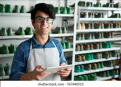 Successful owner of cobbler shop taking online orders at workplace
