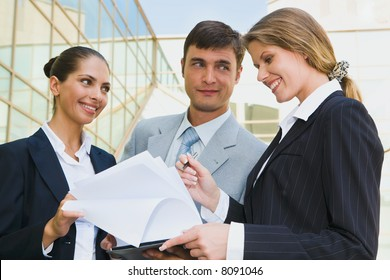 Successful people discussing a plan on the background of building