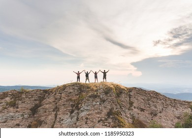 Successful people with raised arms on top of a mountain at sunset. Happy hikers getting on top of the ridge. Nature, outdoors and achievement concepts