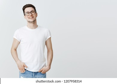 Successful pleased european IT guy celebrating signing good deal with investors, standing proudly smiling broadly, laughing, holding hands in pockets, wearing glasses and t-shirt over grey wall